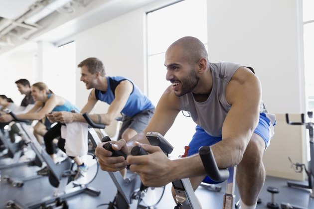 Smiling man enjoying exercise class stationary bike gym
