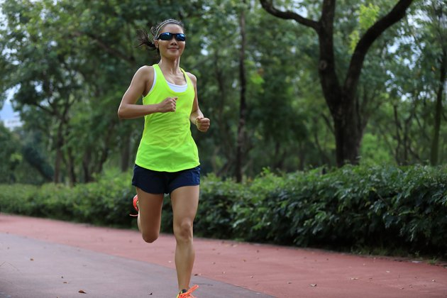 Fitness sporty woman jogger running at outdoors jogging track in park