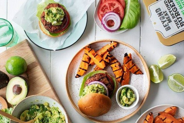 lifestyle shot of food spread with Beyond Meat burgers, sweet potato fries, toppings and guacamole