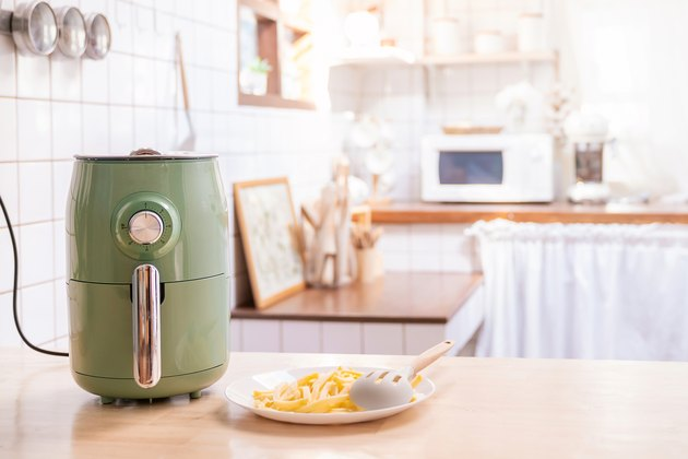 green air fryer on kitchen counter with plate of fries beside it