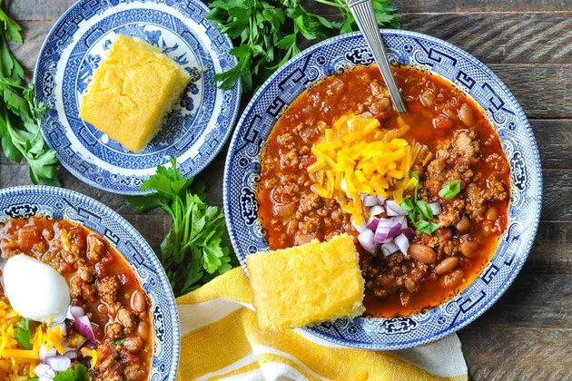 Bowl of turkey chili topped with sour cream, cilantro, red onion, shredded cheddar cheese and a slice of corn bread.