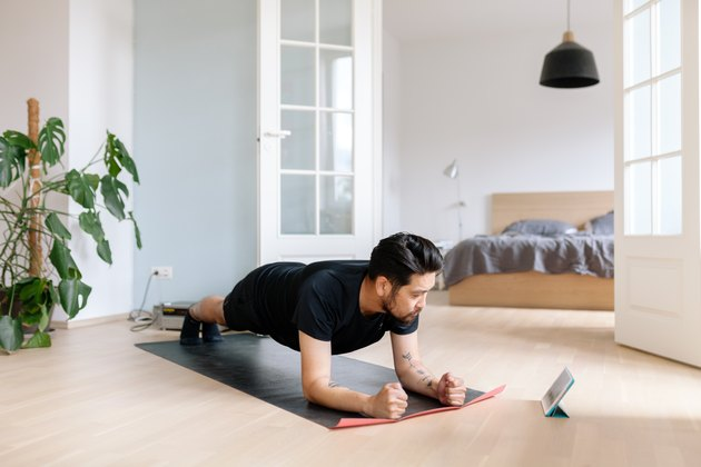 Man uses digital tablet to lean plank position