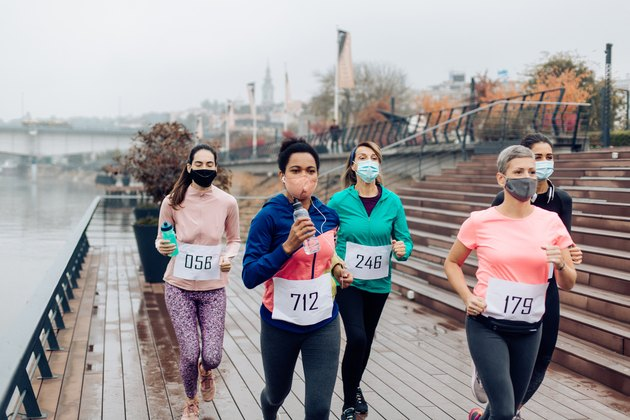 group of runners wearing masks and numbered bibs running a race on a pier