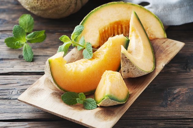 Slices of fresh, potassium-rich cantaloupe melon and sprigs of green mint on wooden cutting board