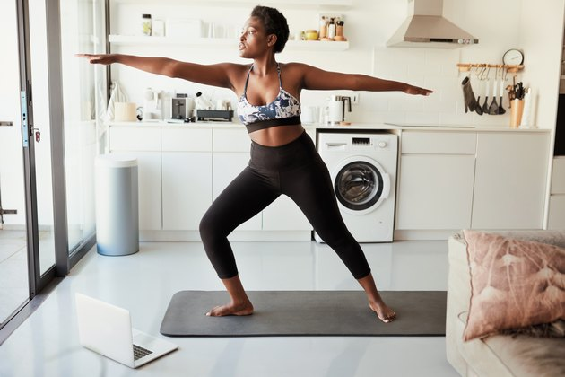 Black woman practicing yoga in a sun-lit room in her home