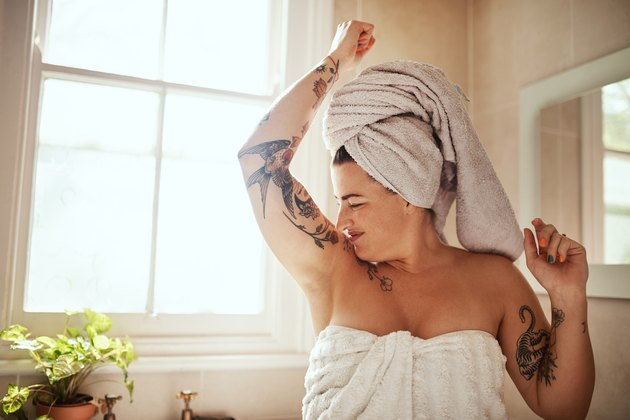 A woman in a bath towel smelling her armpits