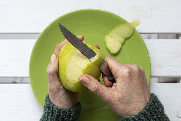 Close-up of female hands peeling a green apple.