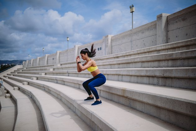 Woman listening to music and exercising on stairs outside