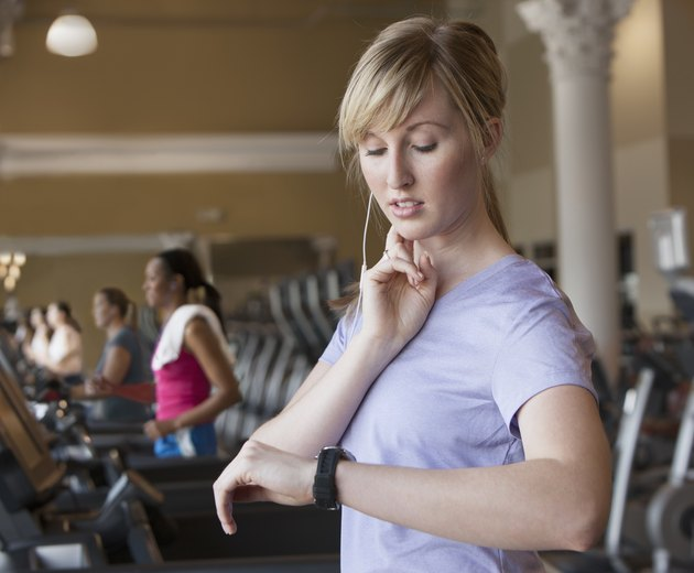 Caucasian woman checking pulse in gym