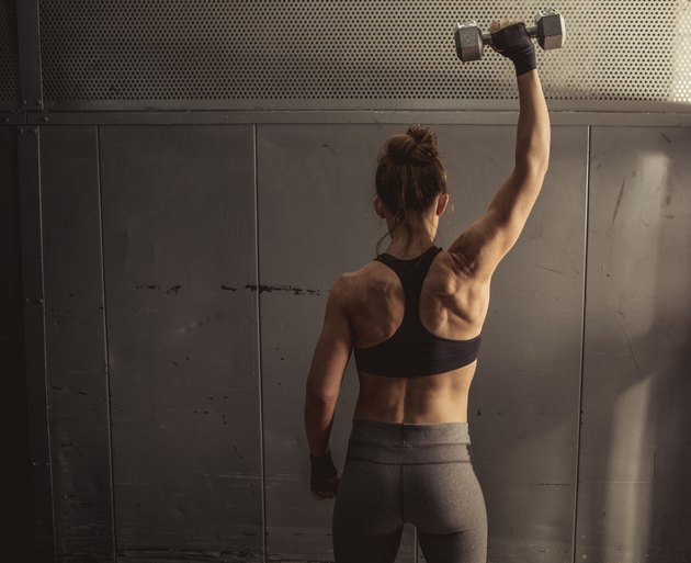Woman doing single-arm shoulder press during her upper-body workout