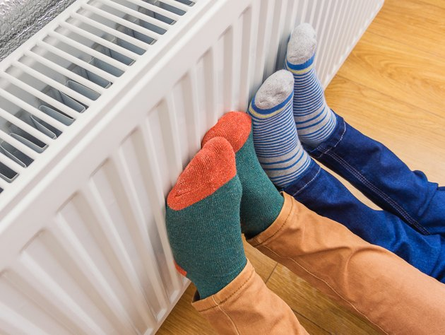 parent and child wearing colorful socks warming cold feet in front of radiator