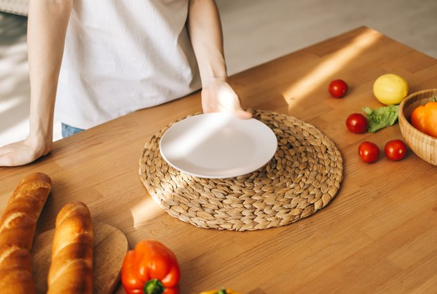 Woman hold empty white plate on the wooden table in the kitchen.