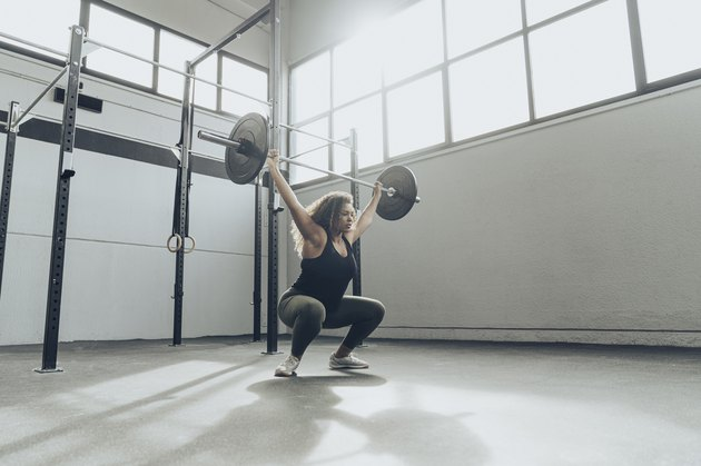 Woman performing overhead squat with barbell in her garage.