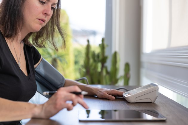Adult Woman checking blood pressure on Auto blood pressure Machine at home