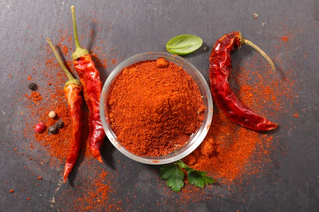 Top view of dried chilis and a bowl of chili powder as a spice for weight loss