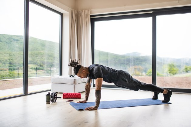 Fit African American man doing planks and muscle-building exercises on a blue yoga mat at home