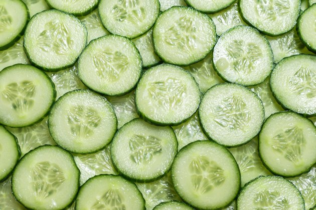 Fresh green slices of cucumber as background.
