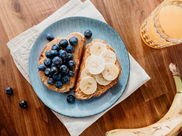 Two toasts with peanut butter, blueberry and banana. Healthy breakfast concept, top view.