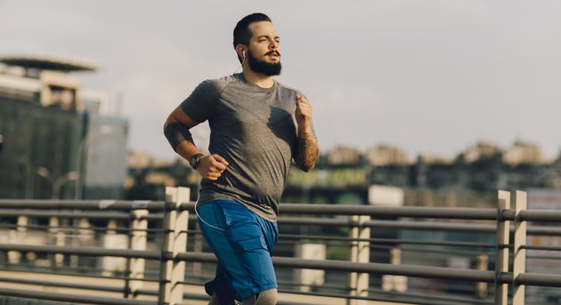 Man going for a run outside across a bridge