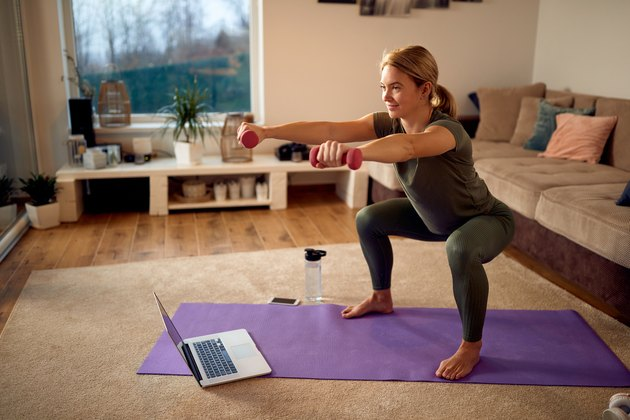 woman doing dumbbell squats on a purple yoga mat in her living room