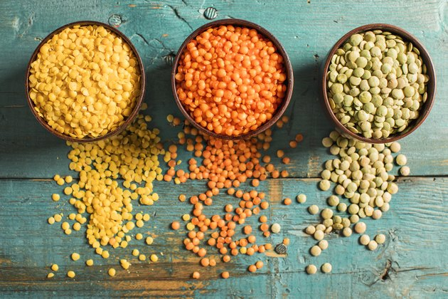 overhead shot of protein-rich red yellow and green lentils on teal wooden table