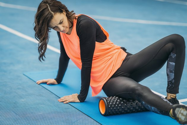 Female Athlete Using a Foam Roller for Workout Recovery