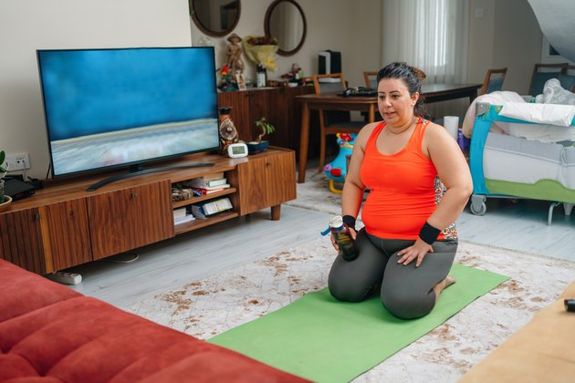 Woman performing workout video at home.