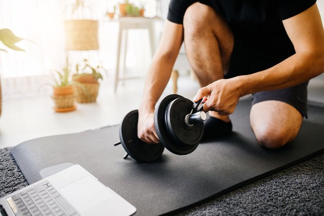 Young sporty man having sports training with dumbbells at home