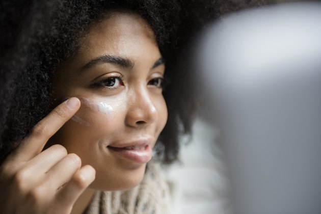 A woman applying zinc oxide ointment to her face to treat dark spots