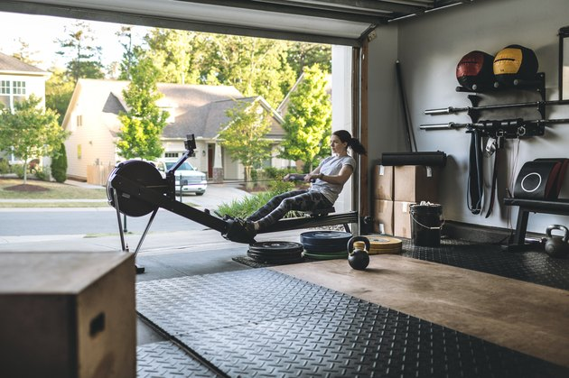 woman exercising on a rowing machine for cardio workout in home gym in garage