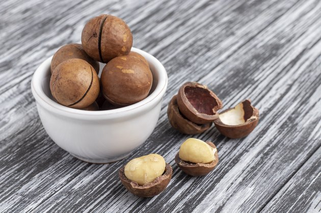 Macadamia nuts in bowl on wooden table.