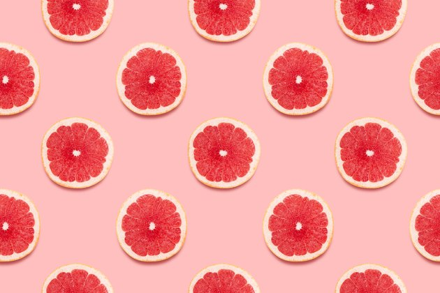 Grapefruit slices in a pattern on a pink background