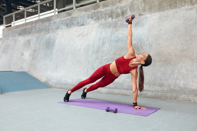 Woman. Plank Workout With Dumbbells. Fitness Girl In Fashion Sporty Outfit With Raising Hand Doing Exercise Against Concrete Wall. Sexy Training Outdoor For Strong Muscular Body.