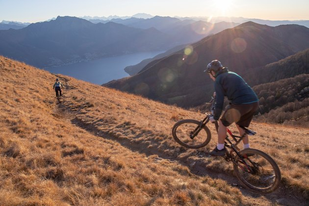 cyclists ride mountain bikes down grassy mountain ridge at sunrise