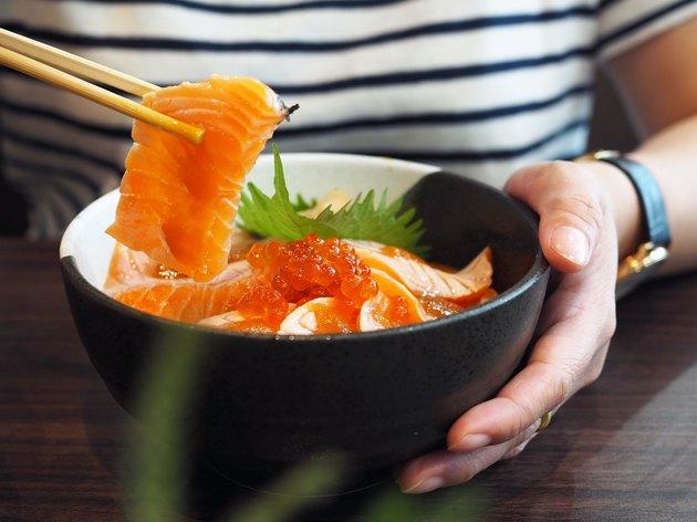 close up of woman using chopsticks in bowl of salmon sashimi