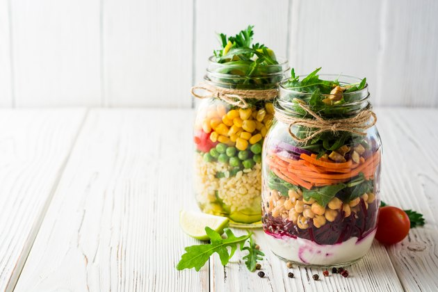 Healthy homemade salads with chickpeas, bulgur and vegetables in mason jars on white wooden background.