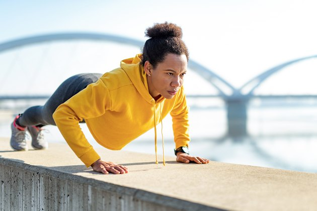 African American woman wearing a yellow hoodie and doing push-ups outdoors