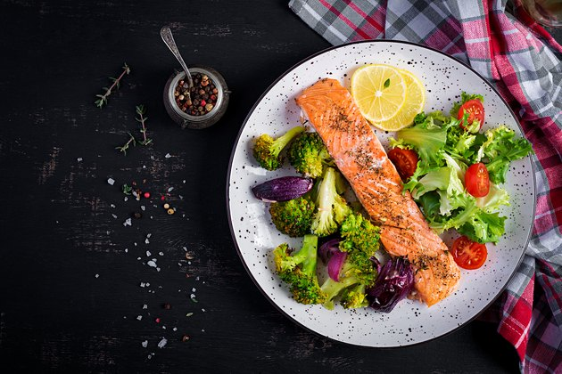 Baked salmon fillet with broccoli, red onion and lemon. Top view, overhead