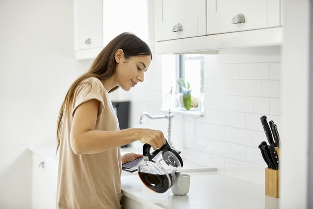 Young woman pouring coffee in cup at home
