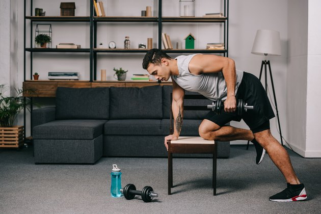 strong bi-racial man doing exercise with dumbbell on chair in living room