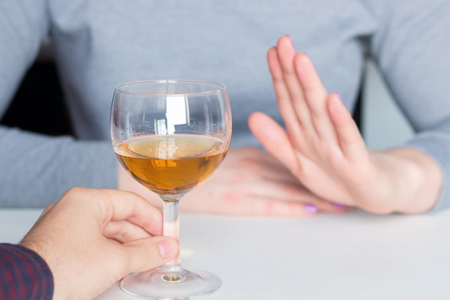 A woman refusing a glass of alcohol as a natural remedy for diarrhea
