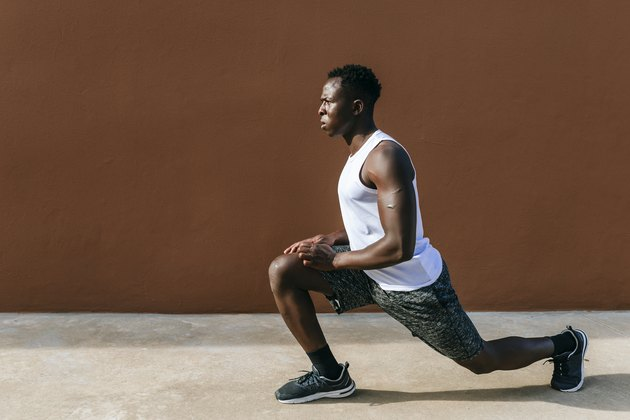 Young man doing stretching exercises against brown wall