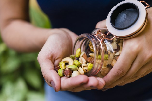Woman's hand holding glass hermetic pot with mix of nuts