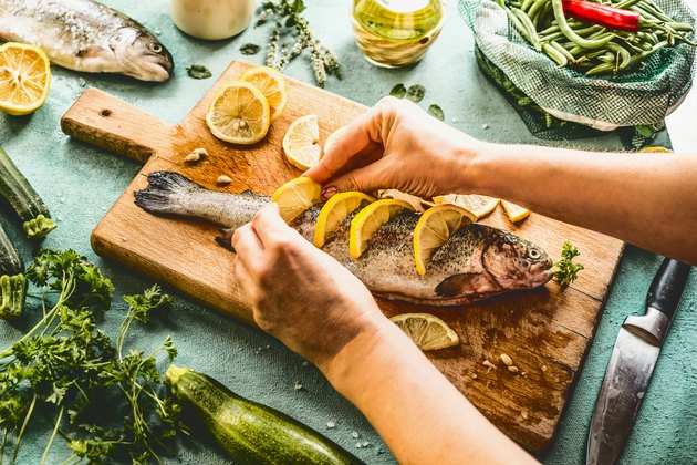 Female woman hands  stuff with lemon raw trout fishes