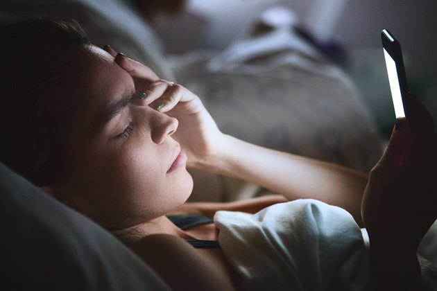 Woman in bed with a headache looking at smartphone