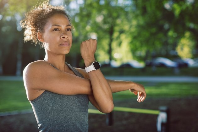 Athletic Black woman stretching her arms outside