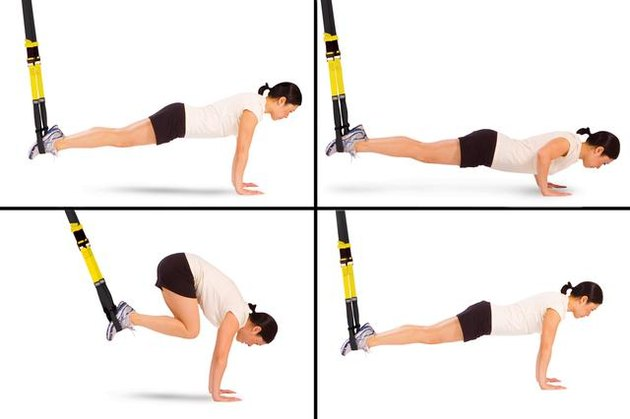 Woman performing atomic push-up with crunch TRX exercise