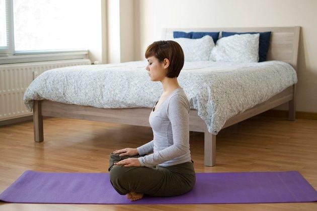Woman demonstrating how to do Lotus pose yoga for sleep