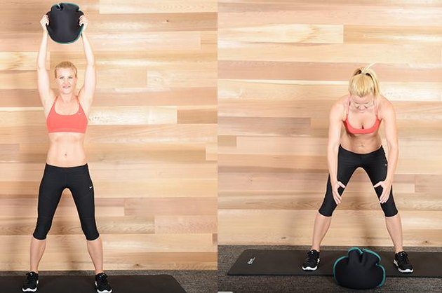 Woman performing medicine ball slam exercise ab exercise.