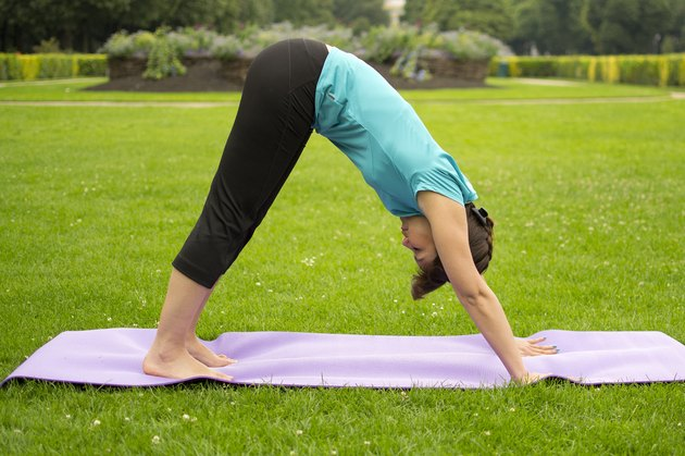 Woman demonstrating how to do the yoga pose Downward Facing Dog (Adho Mukha Svanasana)